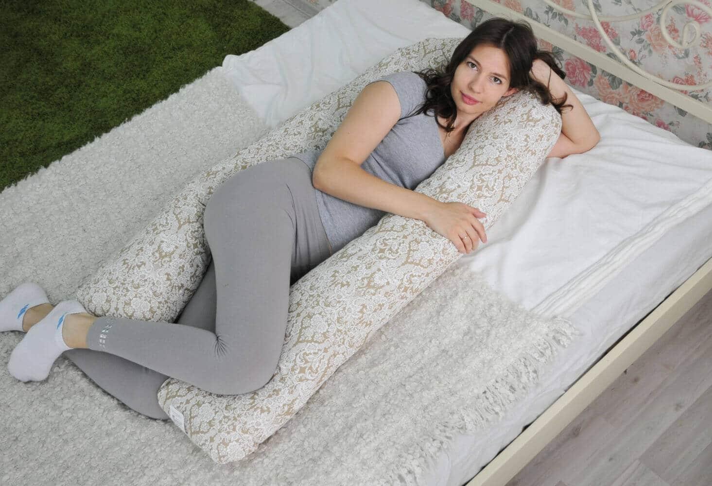 Девушка лежит на подушке для беременных